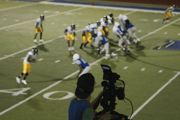 Behind the scenes of cameraman filming wide shot of football play