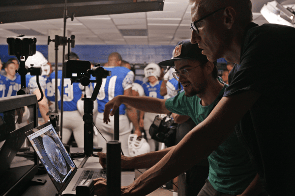 Behind the scenes photo of camera crew in football locker room filming scene