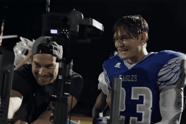 Behind the scenes shot of football player actor with client reviewing footage