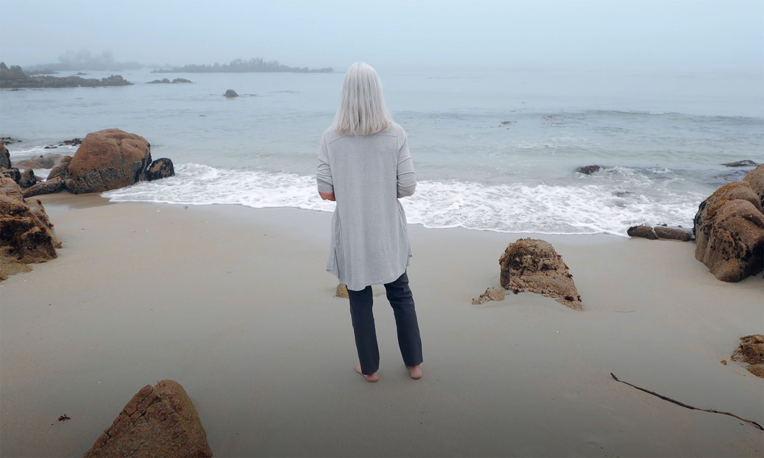Julie Packard on a beach, staring out into the water