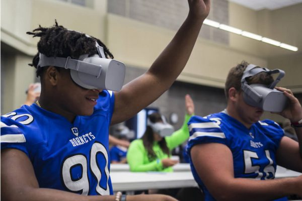 Students in football jerseys sitting at a desk wearing VR headsets